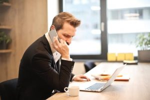 Man talks on phone and looks at laptop